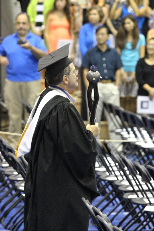 University Registrar John Q. Pierce leads the graduation processional with the university mace